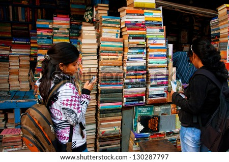 KOLKATA, INDIA - JAN 15: Young female student with a cell phone choose the book on the street market on January 15, 2012 in Kolkata. From 1976 Kolkata have the Book Fair with 2 million visitors annual - stock photo