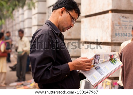 KOLKATA, INDIA - JANUARY 18: Asian man flips through the magazine on the street on January 18, 2012 in Kolkata, India. From 1976 Kolkata have the biggest Book Fair with 2 million visitors every year. - stock photo