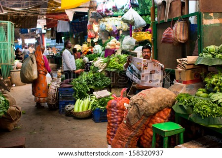 KOLKATA, INDIA - JANUARY 10: Vegetable seller reads a newspaper and waits for the customers on the old city market on January 10, 2012 in Calcutta. 0.81% of Kolkata's workforce employed in agriculture - stock photo