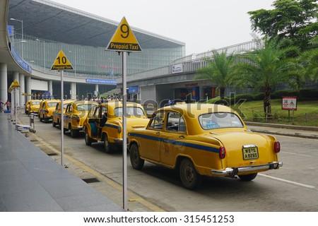 KOLKATA, INDIA - JUL 8, 2015. Yellow Ambassador taxi cars waiting passenger at arrival of International Kolkata airport in Kolkata, India. First Ambassador was produced in 1921. - stock photo