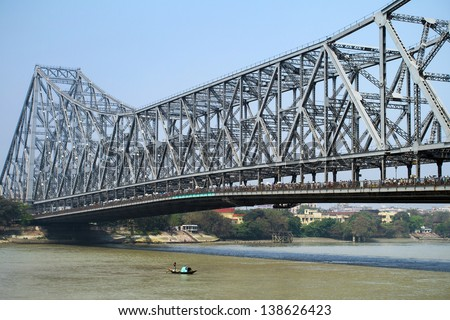 KOLKATA, INDIA - MARCH 13: Fisherman boat crosses the Hooghly River nearby the Howrah Bridge on March 13, 2013. Hooghly Bridge is a famous landmark in the city of Calcutta / Kolkata, India. - stock photo