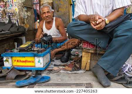 KOLKATA, INDIA - MARCH 14: Unidentified shoe shiner does his job at street of Kolkata on March 14, 2013. Lots of people make their living by doing this job in India. - stock photo