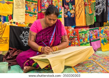 KOLKATA, INDIA - NOVEMBER 28: An Indian craftswoman paints on colorful handicraft items for sale during the annual State Handicrafts Expo 2015 on November 28, 2015 in Kolkata, West Bengal, India. - stock photo