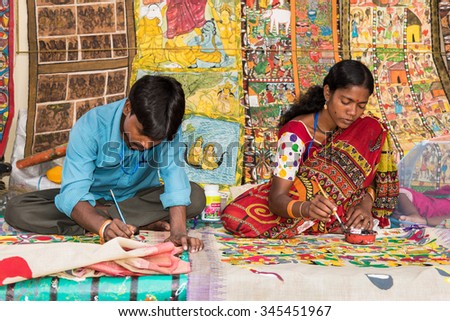 KOLKATA, INDIA - NOVEMBER 28: Indian artist couple paint on colorful handicraft items for sale during the annual State Handicrafts Expo 2015 on November 28, 2015 in Kolkata, West Bengal, India. - stock photo