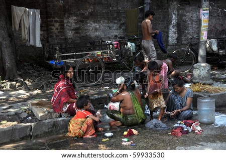 KOLKATA, INDIA - OCTOBER 27:Local people wash themselves on the street of Kolkata on October 27, 2009.  Homeless living on the street are common in every city of India. - stock photo