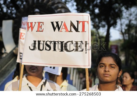 KOLKATA - MARCH 16:School Girls in their uniforms holding signs to seek justice  during a candle light vigil to protest gang rape of an elderly nun on March 16, 2015, at Allen Park in Kolkata, India.  - stock photo