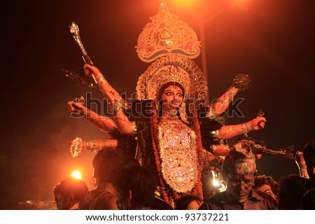 KOLKATA - OCT 17: Devotees bring huge Durga idol for immersing it in river during Durga Puja festival on October 17, 2010 in Kolkata, India. Durga puja is the biggest festival in West Bengal, India - stock photo