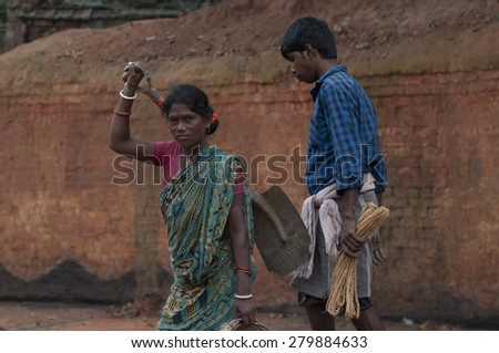 KOLKATA - OCTOBER 26 : A woman worker along with her husband getting ready to work in a brick factory on October 26, 2014 in Kolkata , India. - stock photo