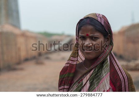 KOLKATA - OCTOBER 26 : A woman worker - one of many women working in brick manufacturing industry where they live and work under unhealthy and unsafe conditions on October 26, 2014 in Kolkata , India. - stock photo