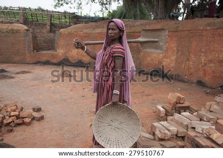 KOLKATA - OCTOBER 26 : A woman worker stepping inside a brick factory to work before the production season begins on October 26, 2014 in Kolkata , India.  - stock photo