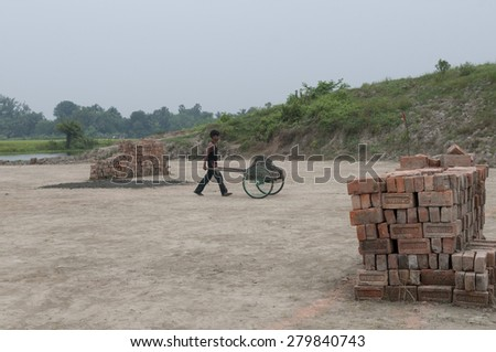 KOLKATA - OCTOBER 26 : A worker carrying bricks from  where they work for minimum wage and without any kind of social security on October 26, 2014 in Kolkata , India. - stock photo