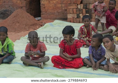 KOLKATA - OCTOBER 26 : Children of brick factory workers sitting inside a factory before the production season begins on October 26, 2014 in Kolkata , India. - stock photo
