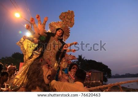 KOLKATA - OCTOBER 18: Devotees taking the huge Durga idol to immerse in the river during Durga Puja festival on October 18, 2010 in Kolkata, India. - stock photo