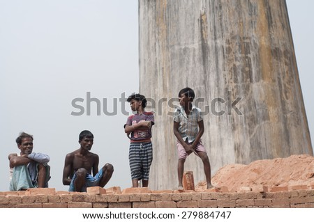 KOLKATA -OCTOBER 26:Workers and their family members standing on stacks of bricks in a brick factory where they work and stay under tough and unhealthy conditions on October 26,2014 in Kolkata,India. - stock photo