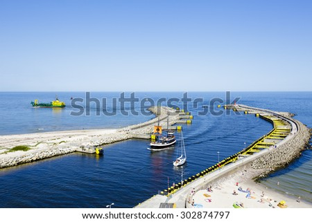 KOLOBRZEG, POLAND - JULY 17, 2015: Breakwater of the seaport, opened after the reconstruction of the entrance to the port of Kolobrzeg in 2012 - stock photo