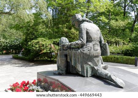 KOLOBRZEG, POLAND - JUNE 22, 2016: Statue of the woman, who cares for a wounded soldier is a tribute to the women who fought during World War II for the Homeland's liberty in the ranks of Polish Army - stock photo