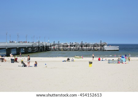 KOLOBRZEG, POLAND - JUNE 19, 2016: Unidentified tourists enjoy a sunny day on the sandy beach and the others have their coffee time at the cafe located at the end of the pier - stock photo