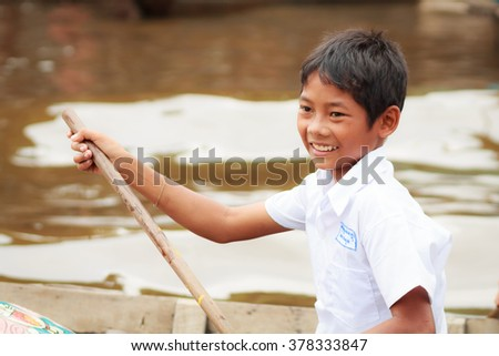 KOMPONG PHLUK, CAMBODIA - OCTOBER 24: Boy of Kompong Phluk rowing boats to come home from school on October 21, 2015 in Kompong Phluk, Cambodia - stock photo