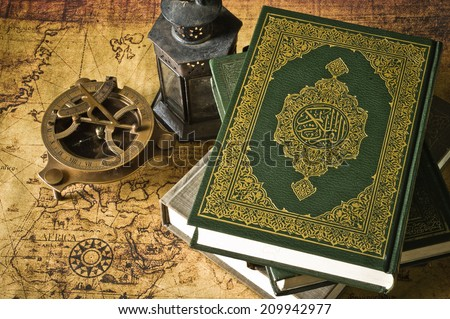 Koran - holy book of Muslims  with  lantern and compass the old map - stock photo