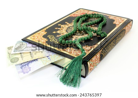Koran with Egyptian banknotes in front of white background - stock photo