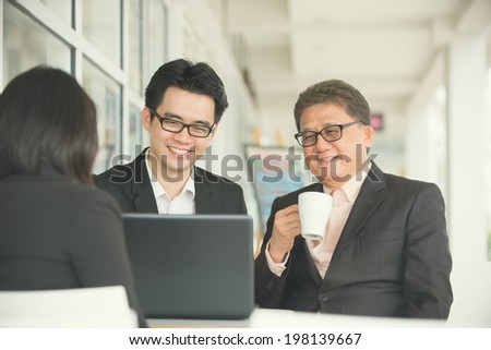 Korean business people gathered together at a table discussing an interesting idea restaurant - stock photo