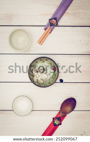 Korean chopsticks, wooden spoon and small traditional plates - stock photo
