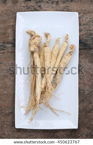 Korean ginseng on wood background,Dry ginseng roots. - stock photo