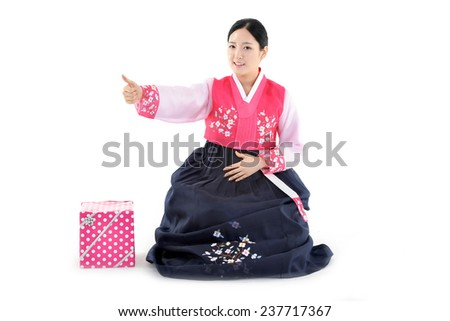 Korean woman sitting on white floor with gift isolated on white background  - stock photo
