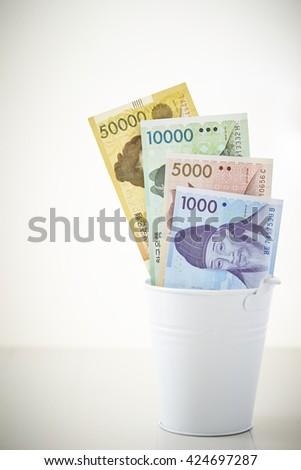 Korean won bills in bucket - stock photo