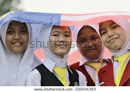 """Kota Kinabalu, Sabah. September 15, 2105 : Four primary school girls standing under the Malaysian National Flag also known as """"Jalur Gemilang"""" during Malaysia Day celebration at Sk. Kolombong. - stock photo"""