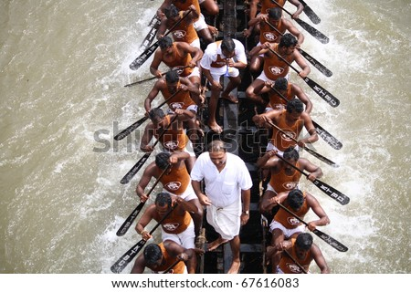 KOTTAYAM, INDIA - AUGUST 29 : Oarsmen in a snake boat team actively in the Kottayam Boat race on August 29, 2010 in Kottayam, India. - stock photo