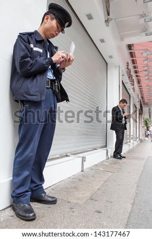 KOWLOON, HONG KONG -Â?Â? MARCH 16: Unidentified Police officer takes notes while unidentified businessman texts on smartphone in Kowloon, Hong Kong on March 16th, 2013.  - stock photo