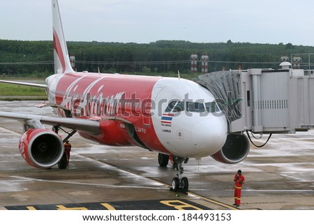 KRABI - JUL 6: An AirAsia aircraft waits at a terminal gate at Krabi International Airport on Jul 6, 2012, in Krabi, Thailand. AirAsia is Asia's largest low-cost carrier flying to 88 destinations. - stock photo