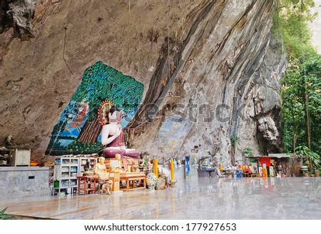 KRABI, THAILAND - DEC 10, 2013: Buddha statue in a rock in the ancient forest. Tiger Temple (Wat Tham Suea) . Temple is one of the most sacred Buddhist sites in the province - stock photo