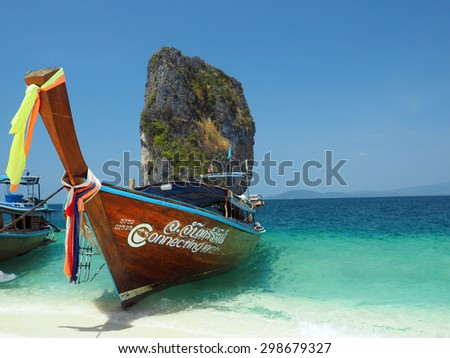 KRABI, THAILAND - FEBRUARY 15, 2015: Traditional Thai wooden longtail boat waits on the shore of Bamboo Island for passengers on a day trip from Phi Phi Island. - stock photo