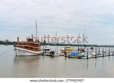 KRABI, THAILAND - 15 OCT 2014: Beautiful, teakwood, luxury tour boat docked at a harbor with other boats on a cloudy day. - stock photo