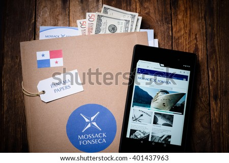 KRAKOW, POLAND - APRIL 5, 2016 : Paper folder with Mossack Fonseca logo with US and EU currency and tablet showing Mossack Fonseca web site. - stock photo