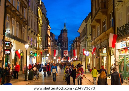 KRAKOW, POLAND - NOV 10, 2014: People walking on Old Town street of Krakow. Krakow Old Town - one of most famous old districts in Poland today and was the center of Poland's political life from 1038 - stock photo
