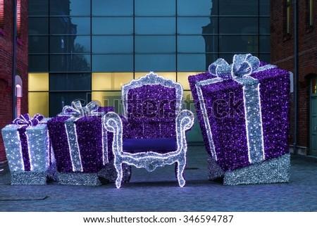 KRAKOW, POLAND - NOVEMBER 24, 2015: Purple trhone and gift boxes - illuminated street decorations for christmas in Krakow, Poland.  - stock photo