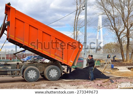 KRASNOGORSK, RUSSIA - APRIL 22, 2015: Construction of new residential area. Builders workers unload truck of hot asphalt for asphalting site - stock photo