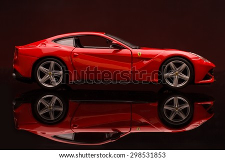 KRIVOY ROG, UKRAINE - JAN 04 - Toy ferrari F12 berlinetta on red backgruond, Saturday 4 January 2014 - stock photo