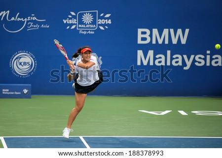 KUALA LUMPUR - APRIL 20, 2014: Chan Yung-Jan of Taiwan returns at the doubles final of the BMW Malaysian Open Tennis in Kuala Lumpur, Malaysia. She partners Zheng Saisai of China to emerge runners-up. - stock photo
