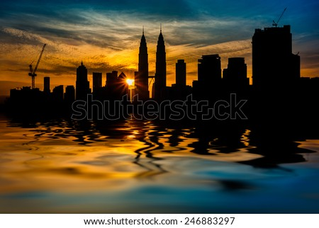 Kuala Lumpur City Center in silhouette during sunrise surrounding with water flood. digital compositing with colour tone, water reflection and ripple effects. - stock photo