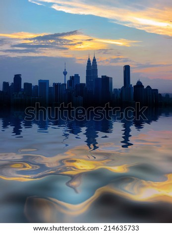 Kuala Lumpur city center with reflection on water during sunset - stock photo
