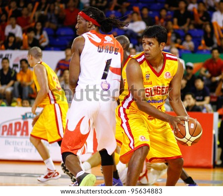 KUALA LUMPUR - FEBRUARY 19: Singapore Slingers' M. Pathman shields the ball from Dragons' Tiras Wade (1) at the ASEAN Basketball League match on February 19, 2012 in Kuala Lumpur. Dragons won 86-71. - stock photo