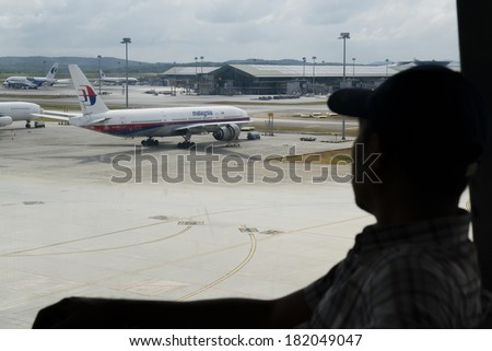 KUALA LUMPUR INTERNATIONAL AIRPORT - MARCH 17: Silhouette of a man with Malaysia Airlines Boeing 777-200ER (9M-MRG)  in the background on March 17, 2014 in KLIA, Sepang, Malaysia. - stock photo