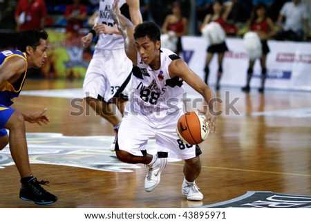 KUALA LUMPUR - JANUARY 05: KL Dragons' Guganeswaran leads the attack on Satria Muda BritAma at the ASEAN Basketball League match January 05, 2010 in Kuala Lumpur. - stock photo