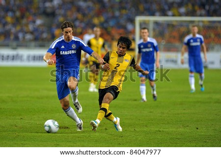 KUALA LUMPUR, July 21 : Chelsea's Fernando Torres (blue) and Malaysian Daudsu Jamaluddin (2) in action during a preseason match agains Malaysia on July 21, 2011 in Kuala Lumpur, Malaysia. - stock photo