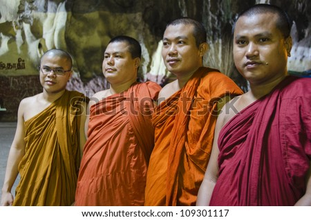 KUALA LUMPUR - JULY 20: Four unidentified Thai Monks pose for pictures inside the Batu Caves in Kuala Lumpur.  The Batu Caves is a Hindu temple and popular visitor attraction, on July 20, 2012 in Kuala Lumpur. - stock photo