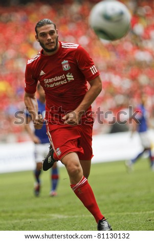 KUALA LUMPUR - JULY 16 : Liverpool football club player Andy Carroll chases  the ball during a friendly match against Malaysia XI on July 16, 2011 in Kuala Lumpur, Malaysia. Liverpool won 6-3. - stock photo